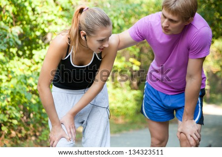 A female jogger with sudden knee-pain - stock photo