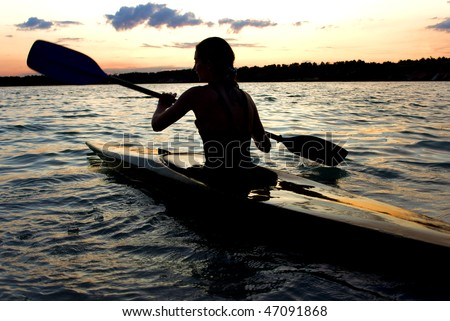 A female kayaker paddles across a lake against sunset