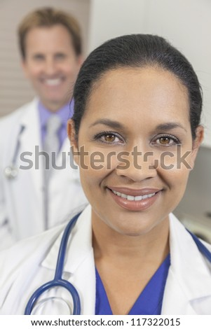 A female latina hispanic doctor in white coat with stethoscope & male colleague behind her