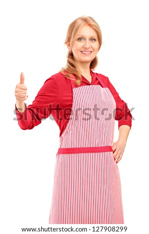 A female manual worker wearing an apron and giving thumb up isolated against white background - stock photo