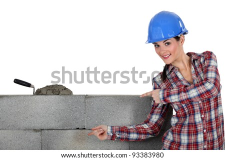 A female mason showing her work. - stock photo