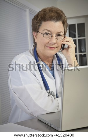 A female medical doctor at her laptop, talking on the phone. - stock photo