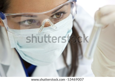 A female medical or scientific researcher or woman doctor looking at a clear solution in a laboratory.