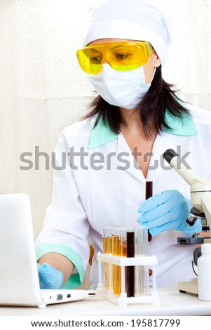 a female medical or scientific researcher or woman doctor looking at a test tube of black solution in a laboratory - stock photo