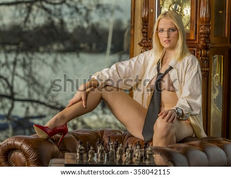 a female model playing chess, posing in erotic positions