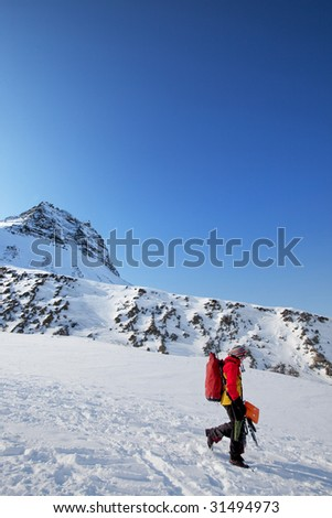 A female mountaineer against a mountain landscape, Svalbard, Norway - stock photo