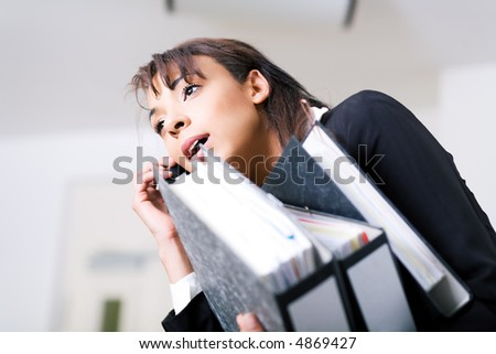 A female office employee carrying files and using cell phone simultaneously