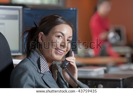 A female office worker talking on the telephone - stock photo