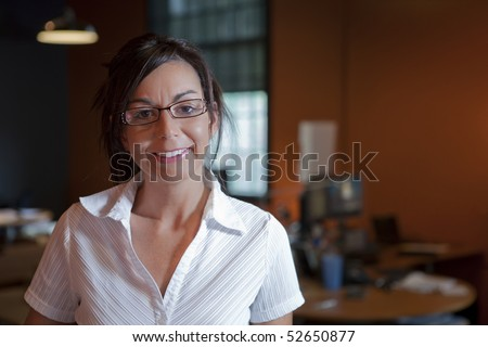 A female office worker wearing eye glasses is standing in an office environment. Horizontal shot. - stock photo