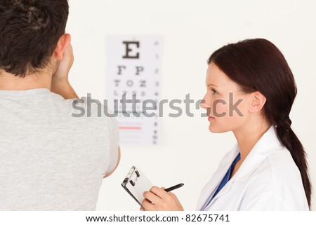 A female optician and man who uses the eye test