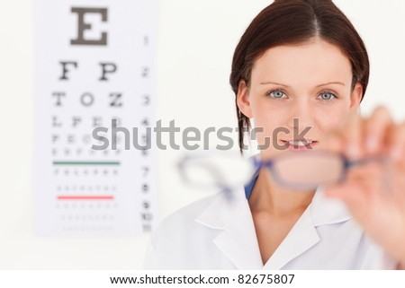 A female optician with eye test showing glasses