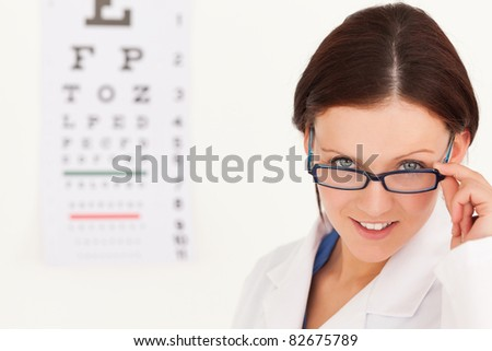 A female optician with glasses and eye test in her office
