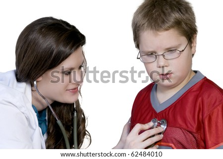 A Female Pediatrician examining a young boy - stock photo