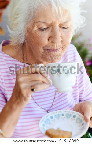 A female pensioner about to sip from her cup of tea