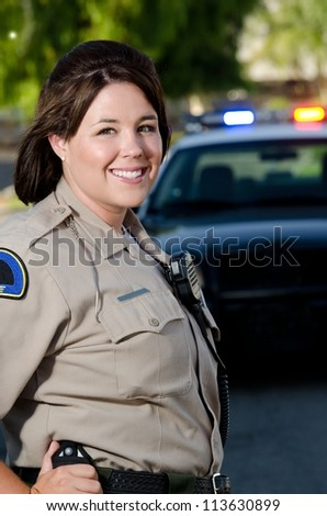 a female police officer smiles while standing in front of her patrol car. - stock photo