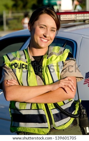 a female police officer smiling as she crosses her arms in front of her partrol car. - stock photo