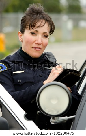 a female police officer standing next to her car as she writes a ticket. - stock photo