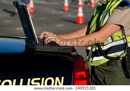 a female police officer types on her lap top computer while on a call. - stock photo