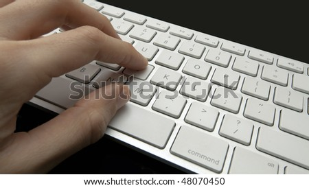 A female presses keys on a keyboard while typing
