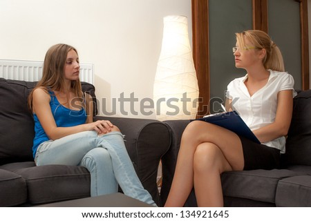 A female psychotherapist treats a teenage female patient with normal and cliche ways. - stock photo