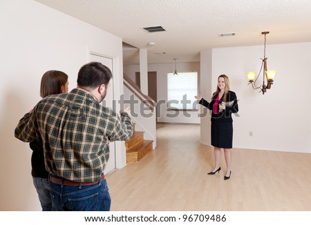A female real estate agent shows an empty home to a husband and wife who are prospective buyers. - stock photo