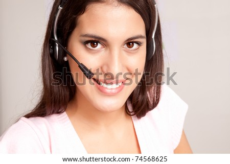 A female receptionist smiling at the viewer talking on the phone - stock photo