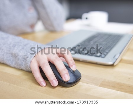 a female's hand clicking a mouse. - stock photo