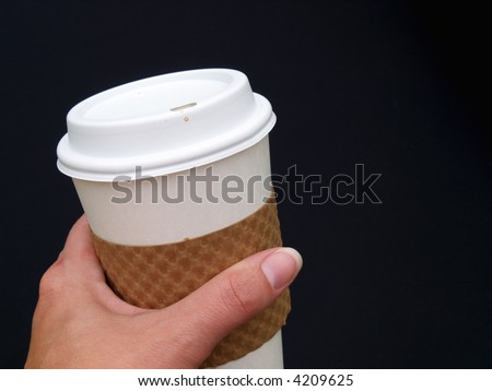 a female's hand holding a disposable paper coffee cup - stock photo