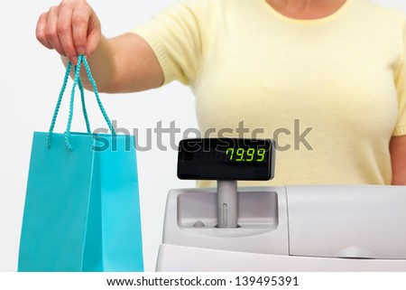 A female sales assistant giving you your purchase in a bag. - stock photo