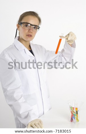 a female scientist examining test tubes with colorful liquids