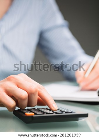 A female secretary or an accountant uses a calculator and takes notes on a paper notebook. Closeup image. - stock photo