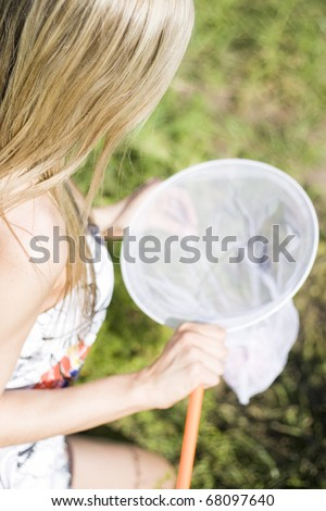 A Female Sitting On Her Knees In A Green Field Looks Into A Butterfly Net While On An Environmental Expedition In Netting Nature - stock photo