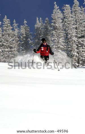 a female skier skiing down a deep powder run in the mountains. The trees are covered in snow