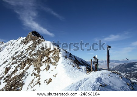 A female snowboarder high on a ridge - stock photo
