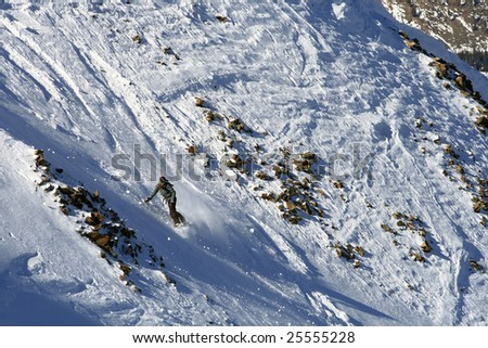 A female snowboarder makes a turn down a steep run. - stock photo