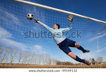 A female soccer player diving to catch the ball - stock photo
