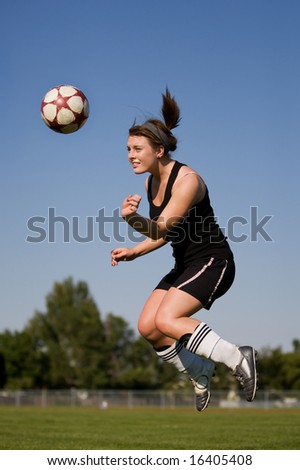 A female soccer player heading the ball