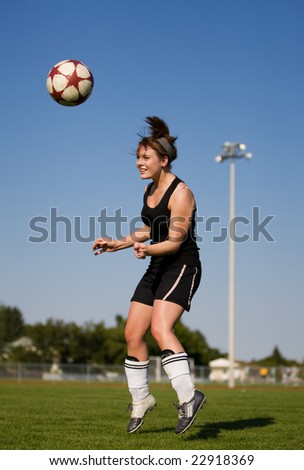 A female soccer player heading the soccer ball
