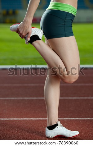 A female sprinter stretching on the running track - side view - stock photo