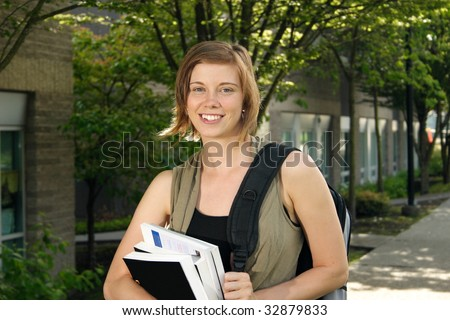 A female student holding books while walking around campus