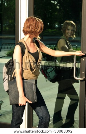 A female student walking in to school smiling at the camera through her reflection