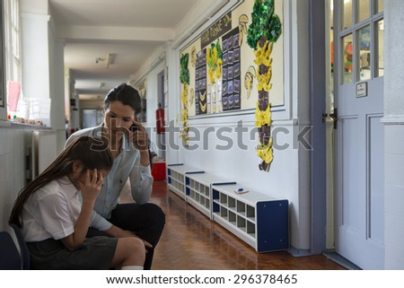 A female teacher sits consoling a young student in the corridor, the little girl looks very upset and holds her head in her hands. - stock photo