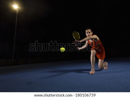 A female tennis player playing a forehand shot, crouching on the ground. / Female Tennis Player, Crouching Forehand - stock photo