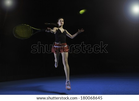 A female tennis player playing a forehand shot, leaping into the air. / female tennis player - stock photo