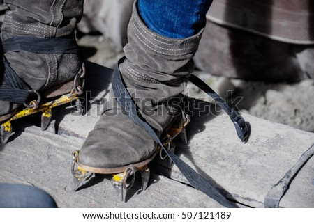 A female tourist putting on ice crampons and getting ready for a glacier walk tour. Hiking and travel..