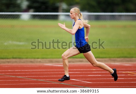 A female track star racing down the track - stock photo