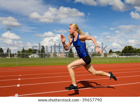 A female track star sprinting down the race track - stock photo