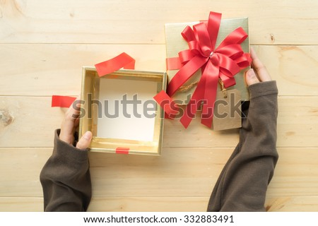 A female two hands opening the empty(blank) gift box on wooden table, top view. - stock photo