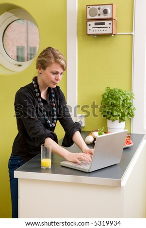 A female uses the computer on the kitchen counter while having a light snack of vegetables