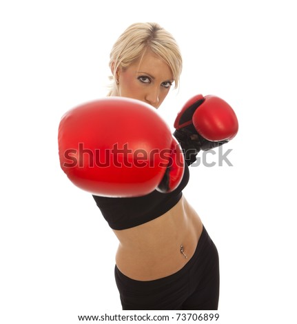 A female wearing red boxing gloves throwing a ounch at the camera - stock photo
